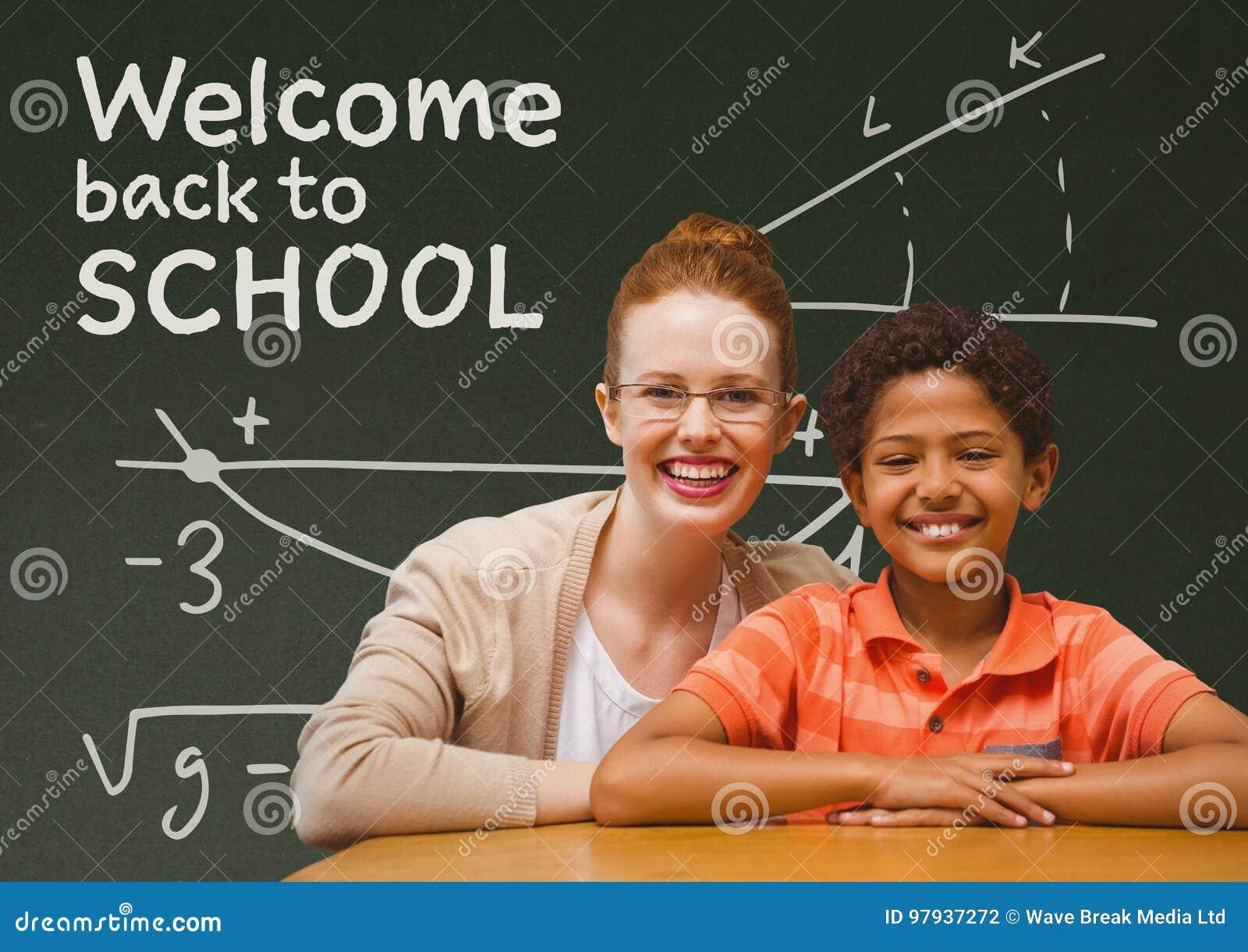学生男孩和老师在桌上反对绿色黑板有欢迎的到学校课文