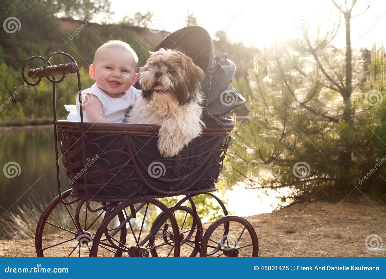 婴孩和小的小狗在摇篮车
