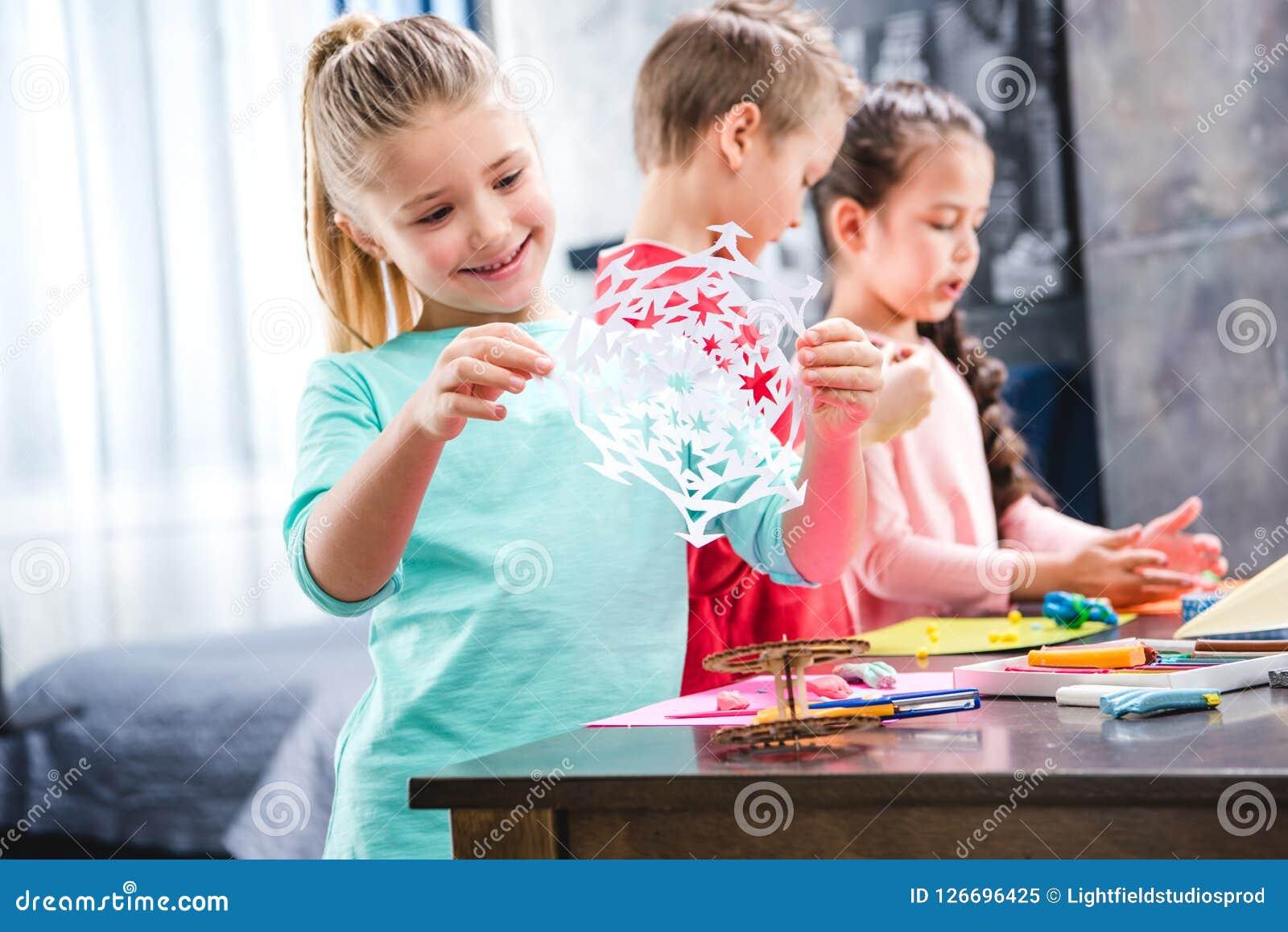 孩子从纸学童的切口雪花