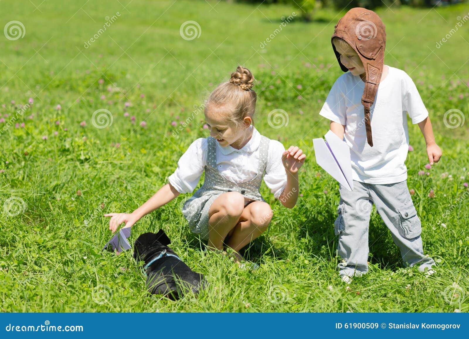 使用与狗(法国牛头犬)的孩子在草 背景兄弟查出的姐妹白色.图片