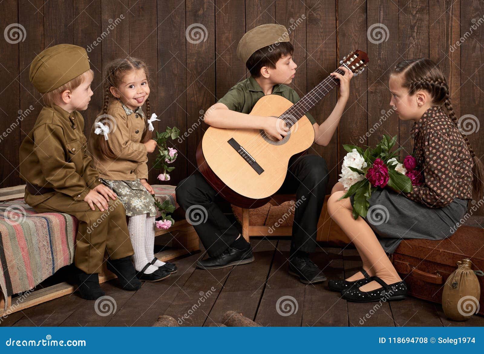 孩子在坐和弹吉他的减速火箭的军服打扮,派遣战士到军队,黑暗的木背景, r