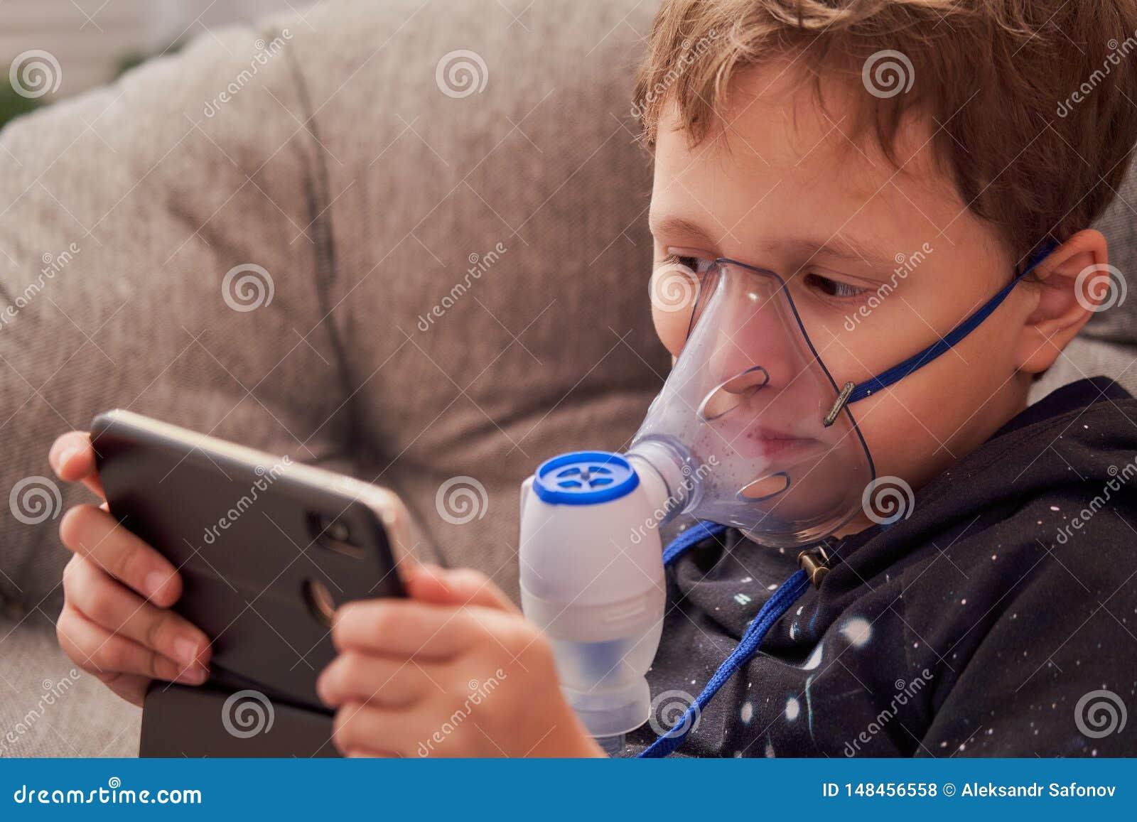孩子在家做吸入雾化器 在面孔佩带吸入蒸气的面具雾化器喷洒了疗程入肺