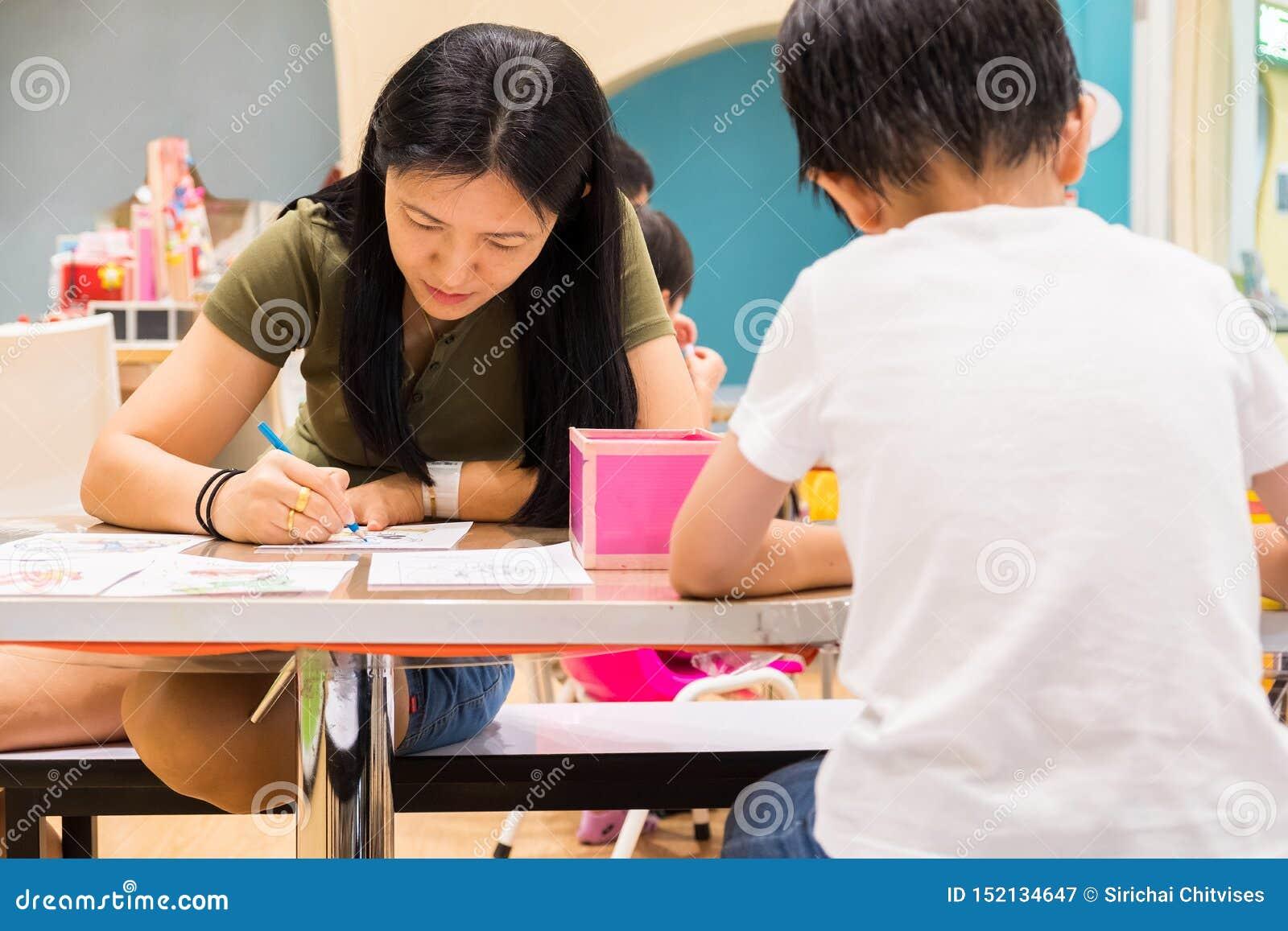 孩子在教室绘与颜色铅笔的画有他们的老师的学会油漆技巧 他们是实践