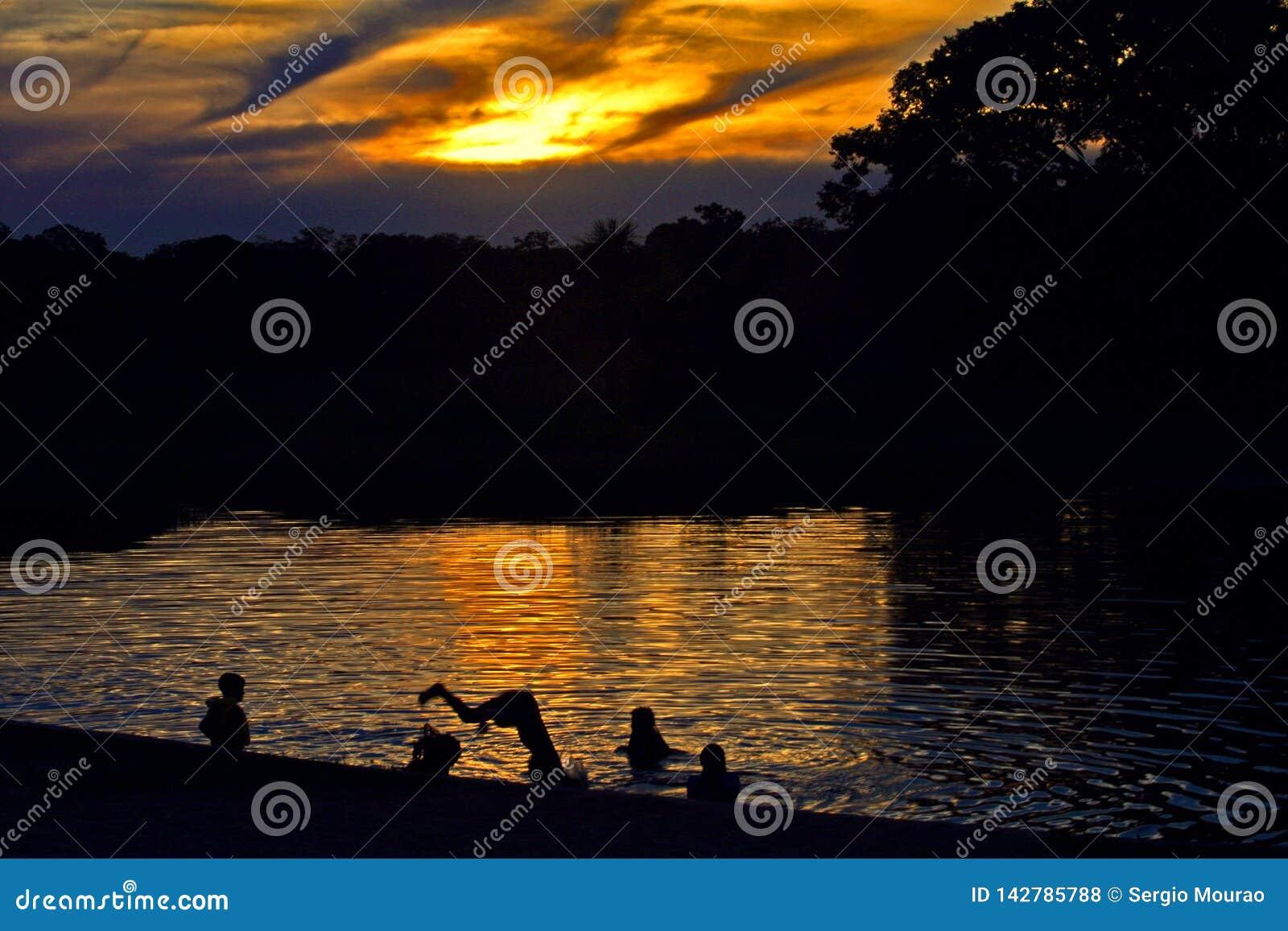 孩子在湖潜水在黄昏