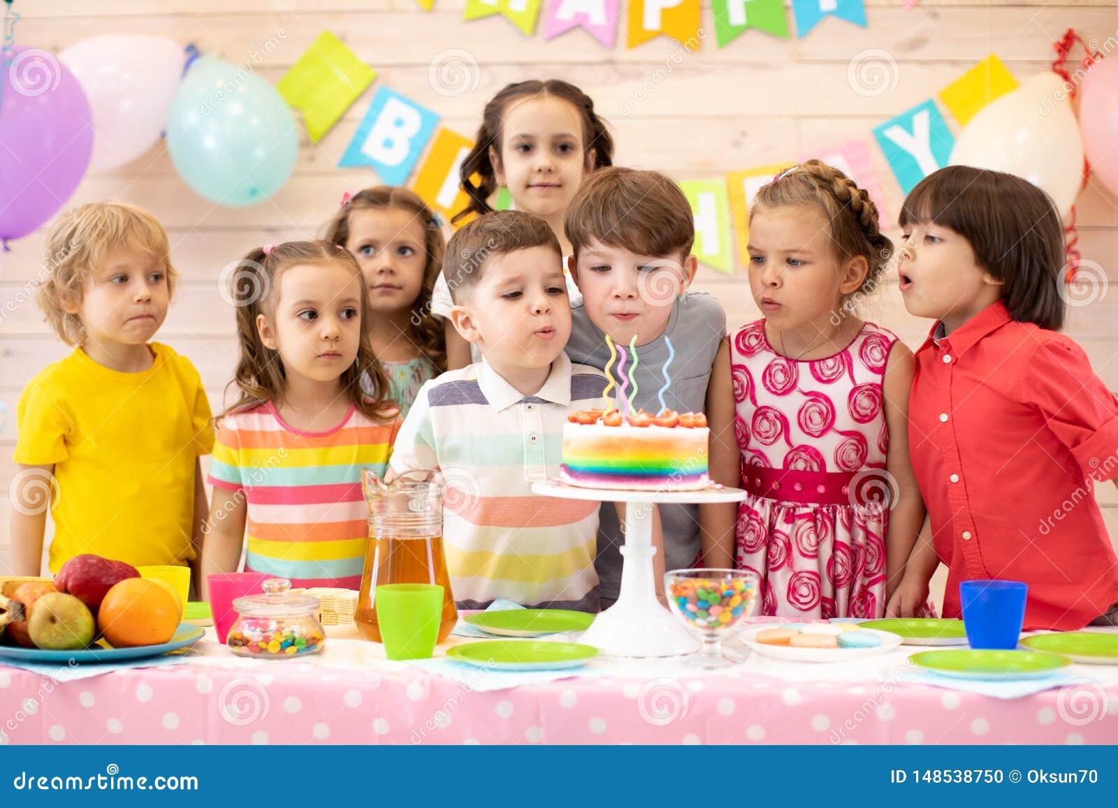 孩子庆祝在欢乐蛋糕的生日宴会和打击蜡烛