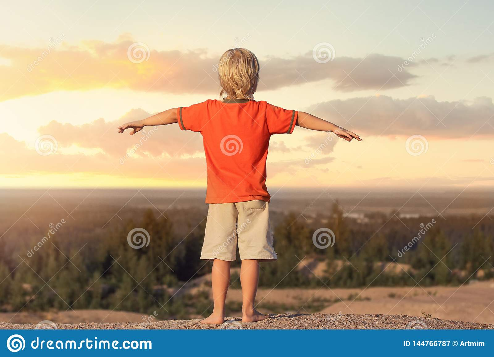孩子男孩举了他的手反对背景日落