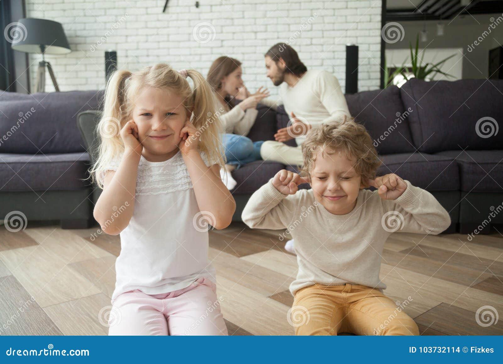 孩子男孩和女孩覆盖物耳朵,父母争论在backgrou