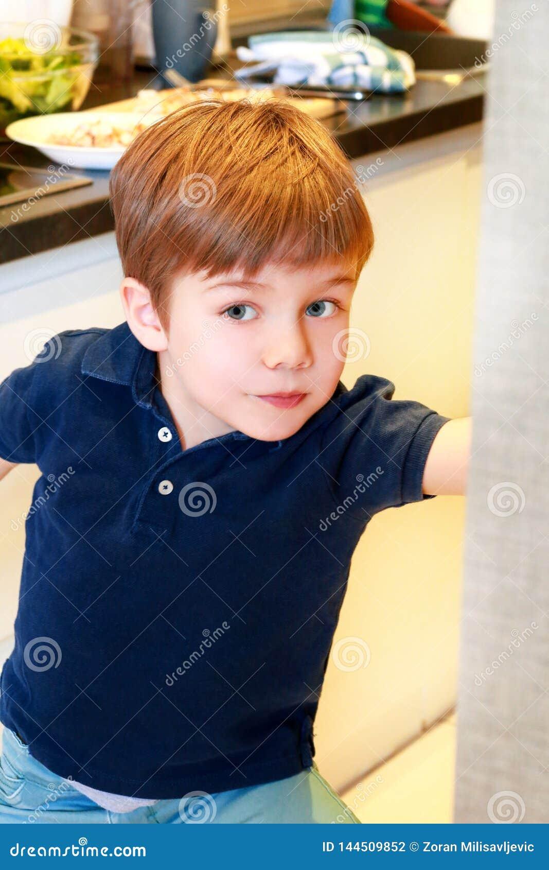 孩子画象在厨房里 逗人喜爱的小男孩,使用在厨房里 小孩饿,看并且检查是它完成的午餐