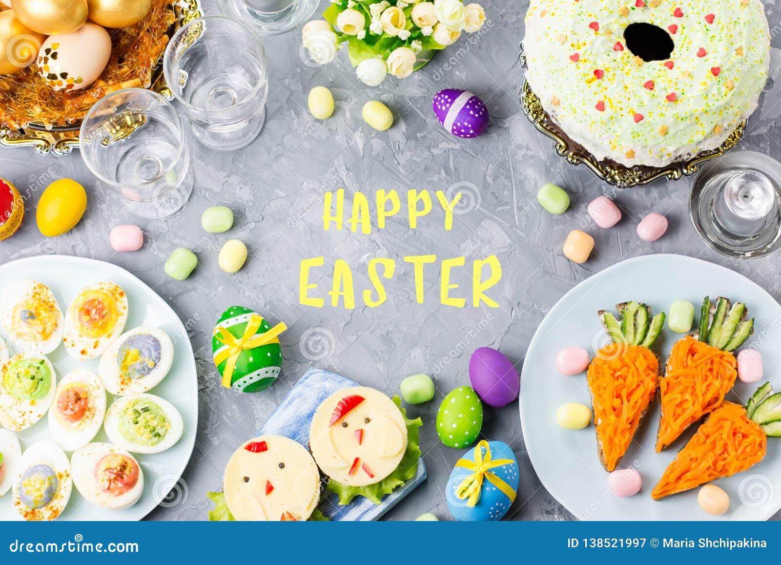 孩子的滑稽的五颜六色的复活节食物与在桌上的装饰 复活节晚餐概念