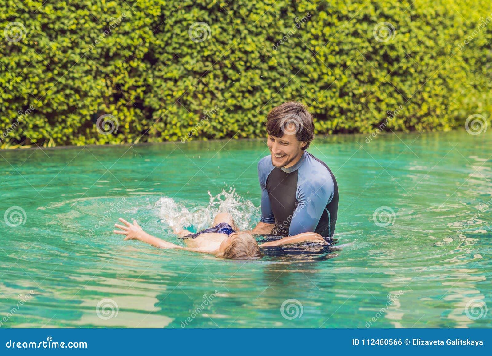 孩子的男性辅导员游泳在水池教一个愉快的男孩游泳