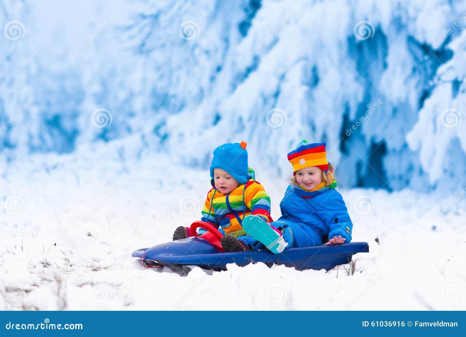 孩子获得在雪橇乘驾的乐趣在冬天