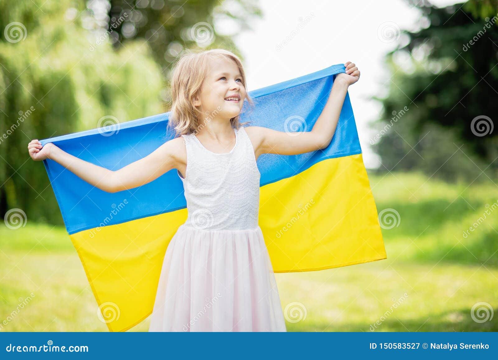 孩子运载振翼乌克兰的蓝色和黄旗领域的 乌克兰的美国独立日 国旗纪念日 宪法天 女孩i