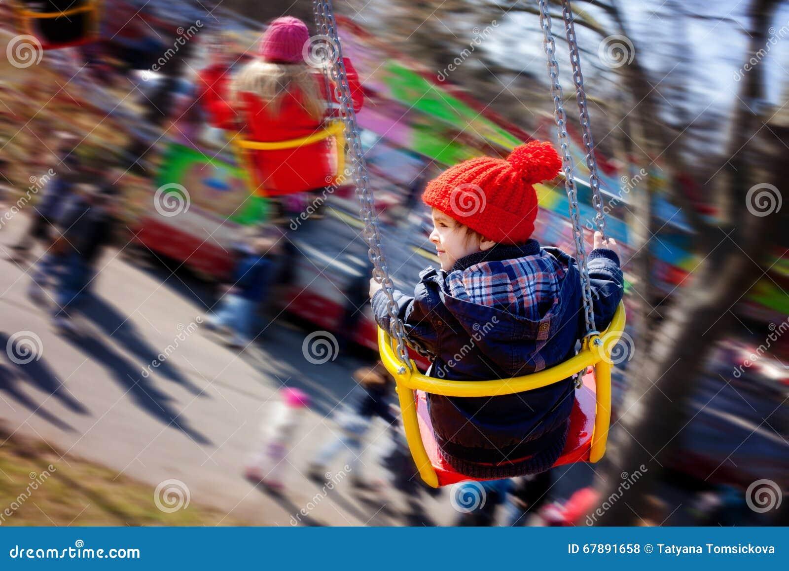 孩子,获得在摇摆链子转盘乘驾的乐趣