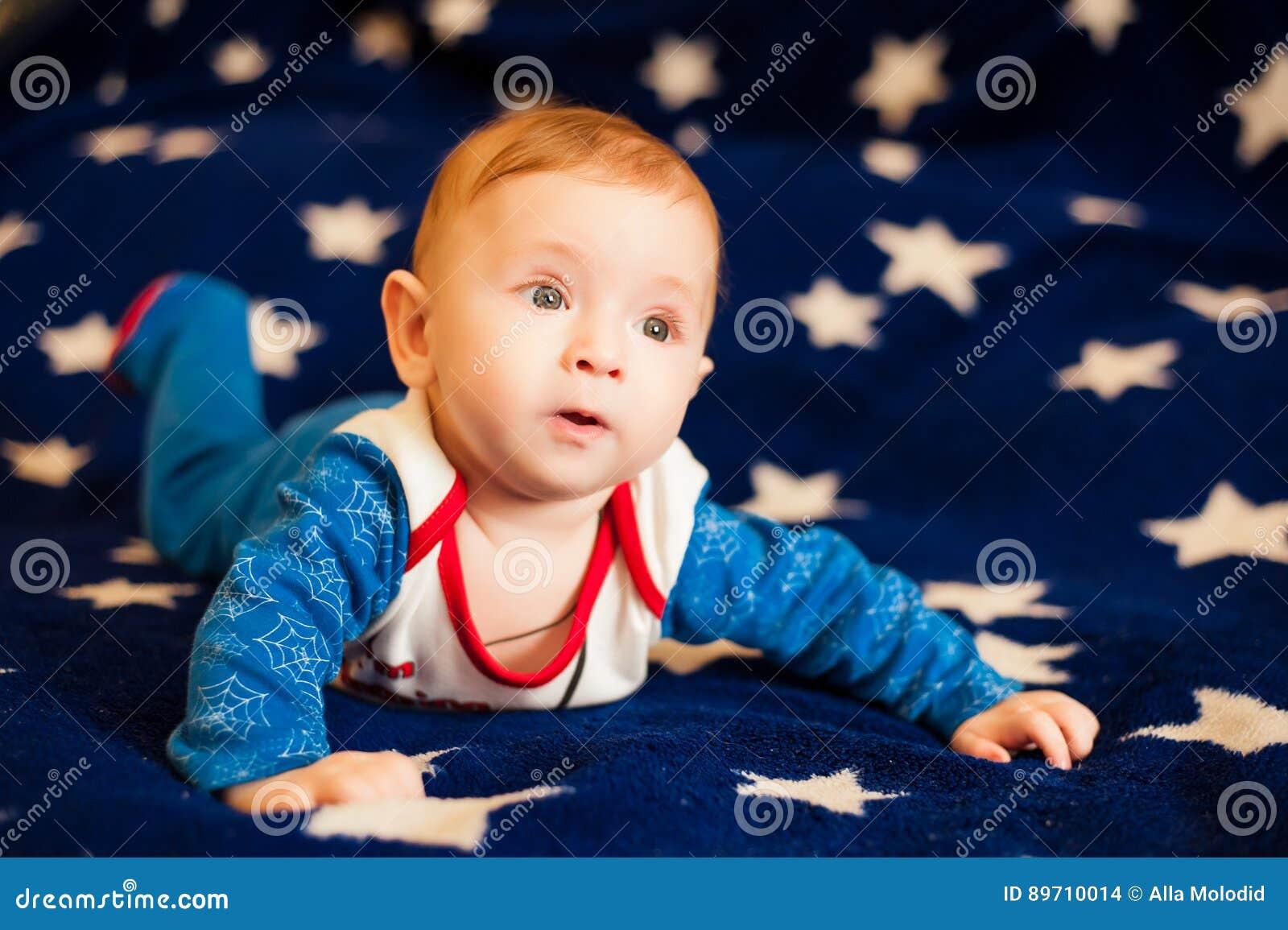 孩子6个月和在家微笑在满天星斗的天空的一条蓝色毯子