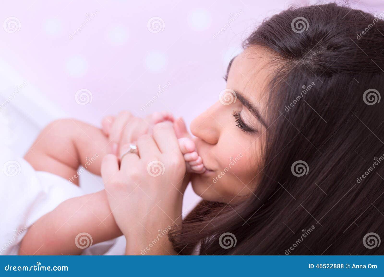 婴孩愉快的亲吻的母亲