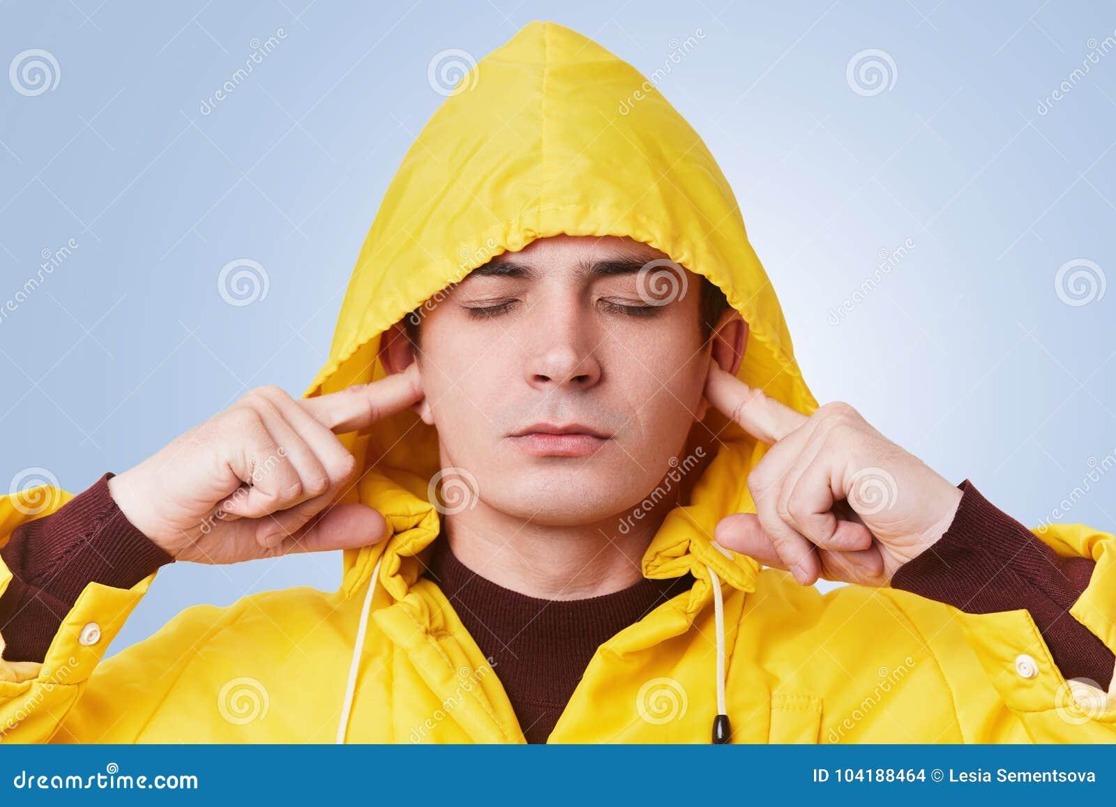 宁静的可爱的男性闭上眼睛并且塞住耳朵,尝试集中,并且听不到喧闹声,佩带在头, isola的黄色敞篷