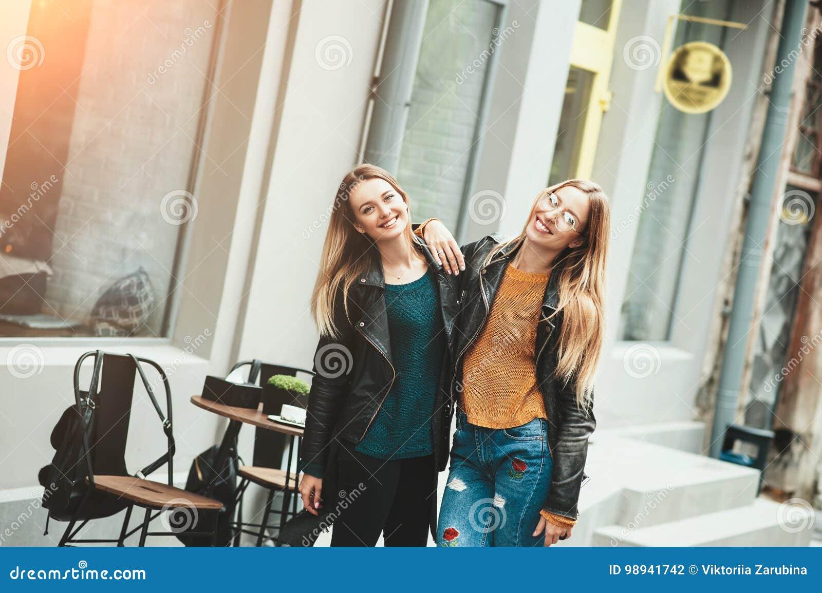 它是与最好的朋友的滑稽的步行!两名美丽的妇女走的室外拥抱和笑在秋天街道上
