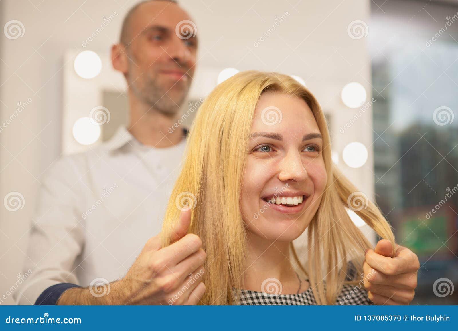 安排的年轻女人她的发型由美发师