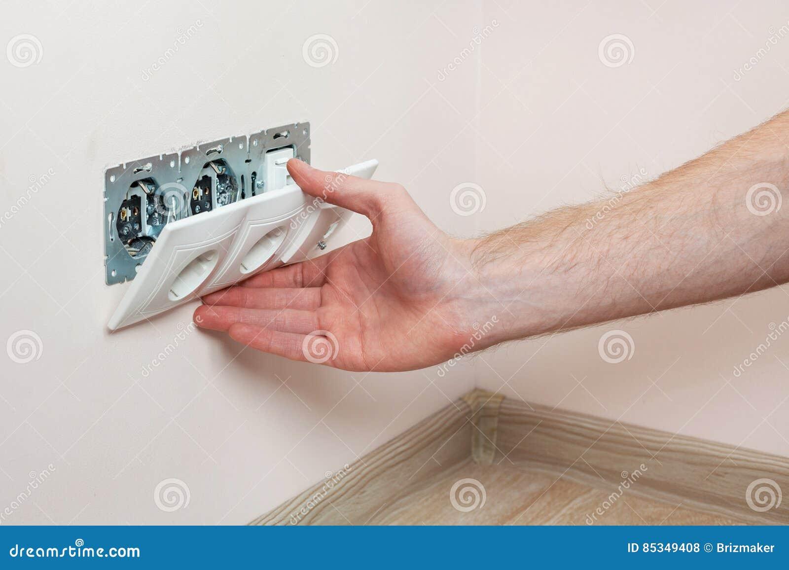 安装墙壁电源插座的电工的手