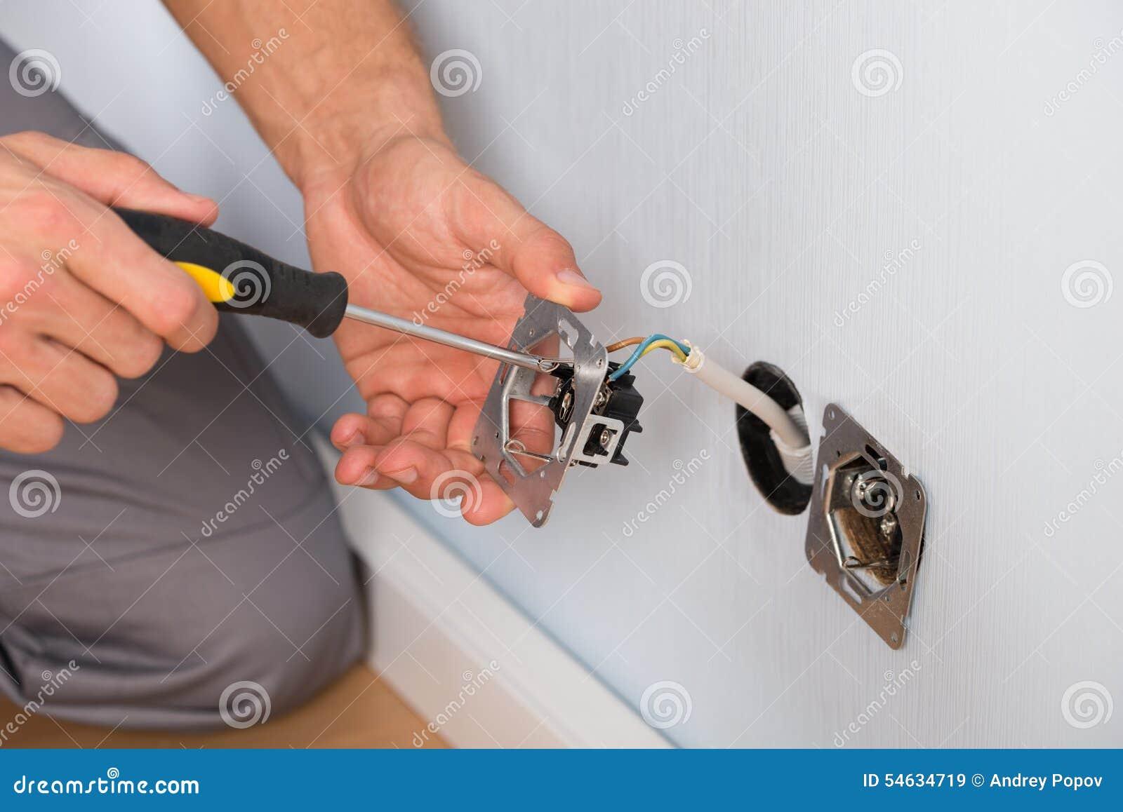 安装壁上插座的电工手