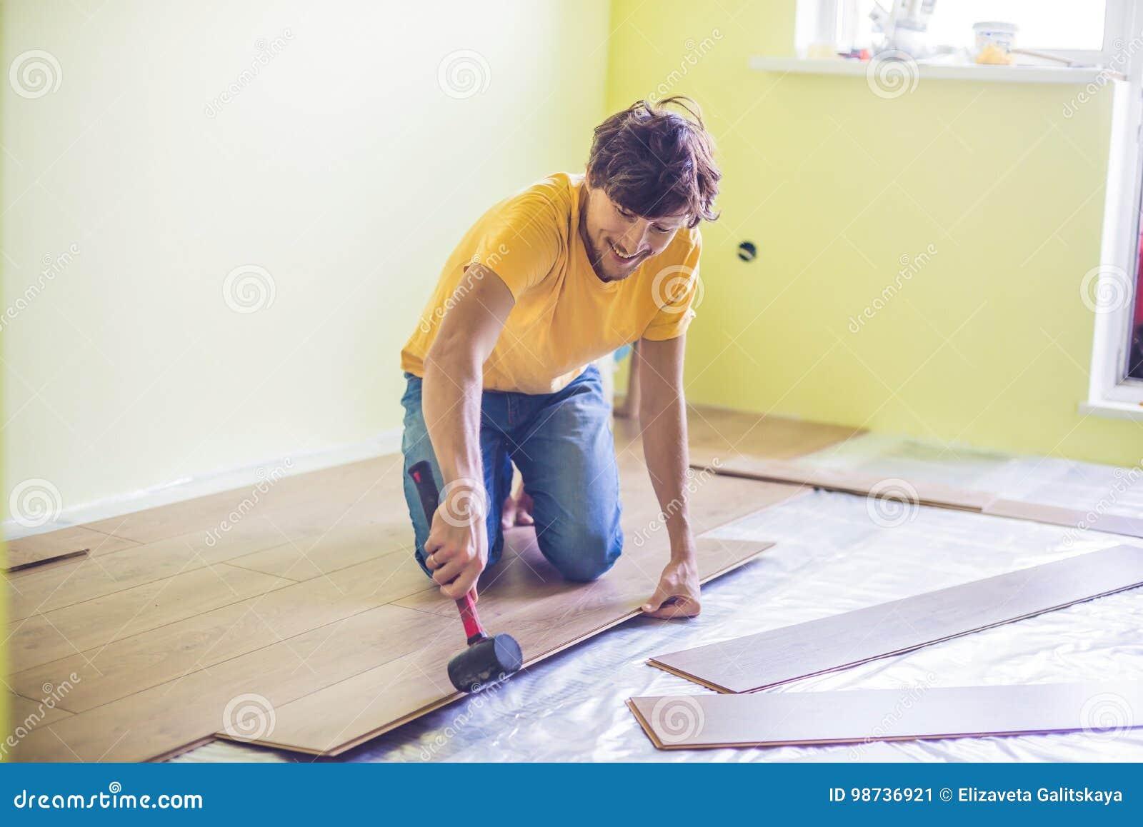 安装新的木层压制品的地板的人 红外地板热