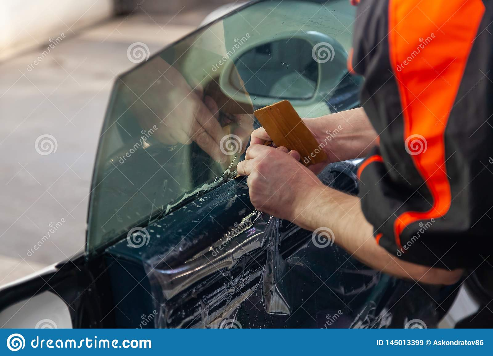 安装的附加设备巫术师在汽车的旁边前面杯黏附色彩影片并且用手铺平它