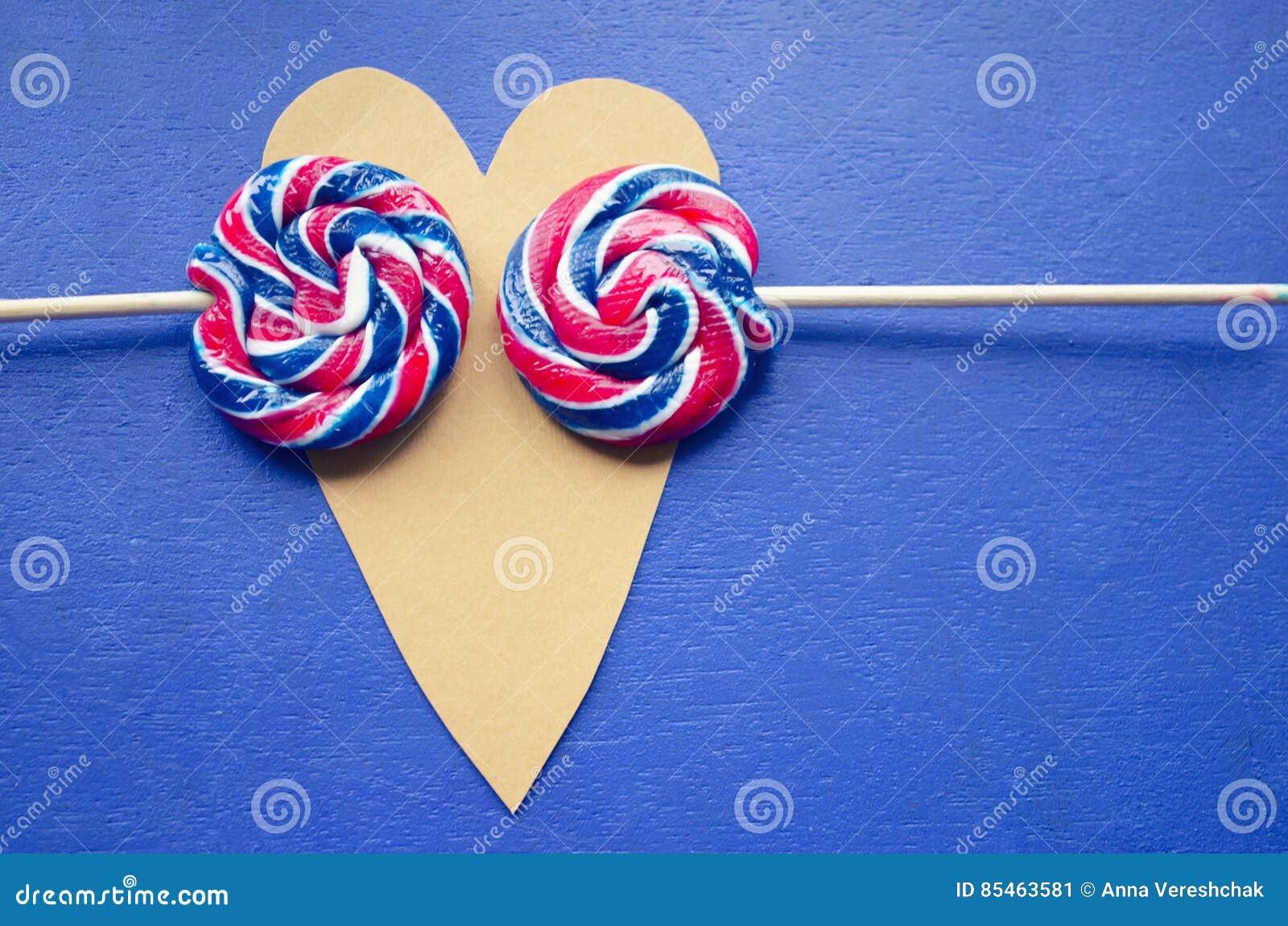 安迪围绕两个棒棒糖的漩涡彩虹在心形 在一根棍子的糖果条纹在蓝色背景 概念亲吻妇女的爱人 2月14日 Ho