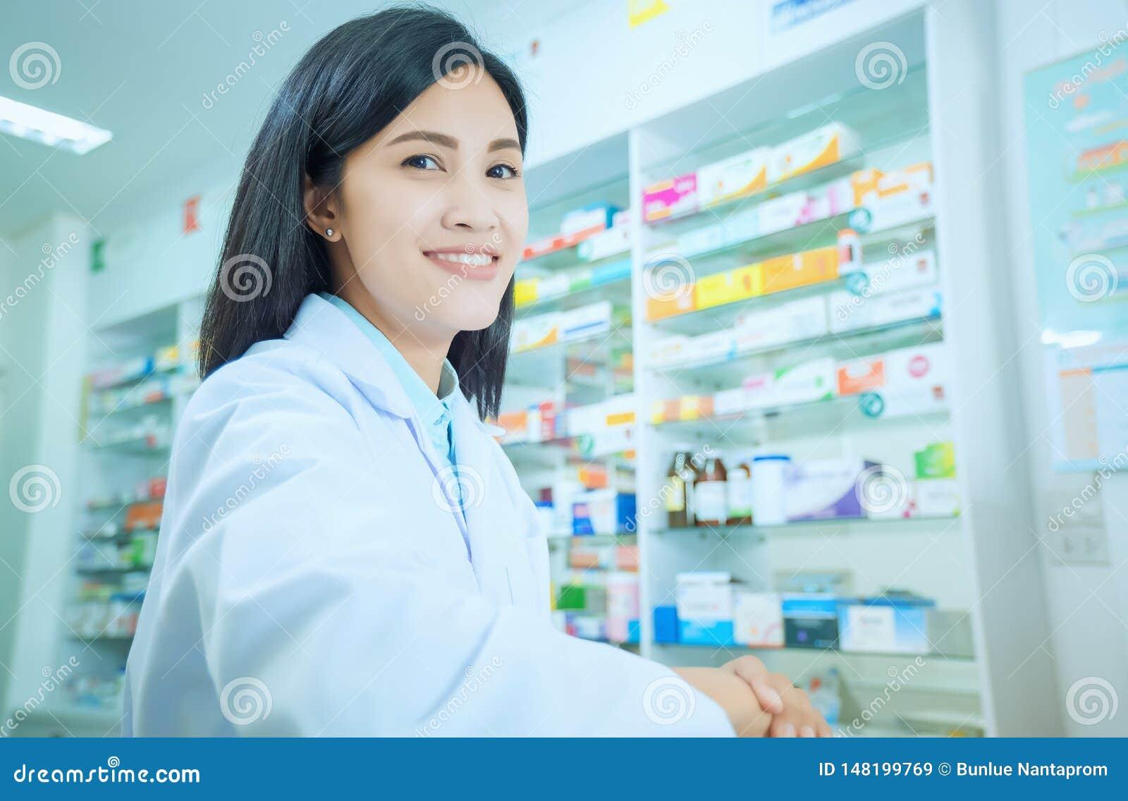 完成他的在药房的美丽的微笑的年轻女人药剂师工作