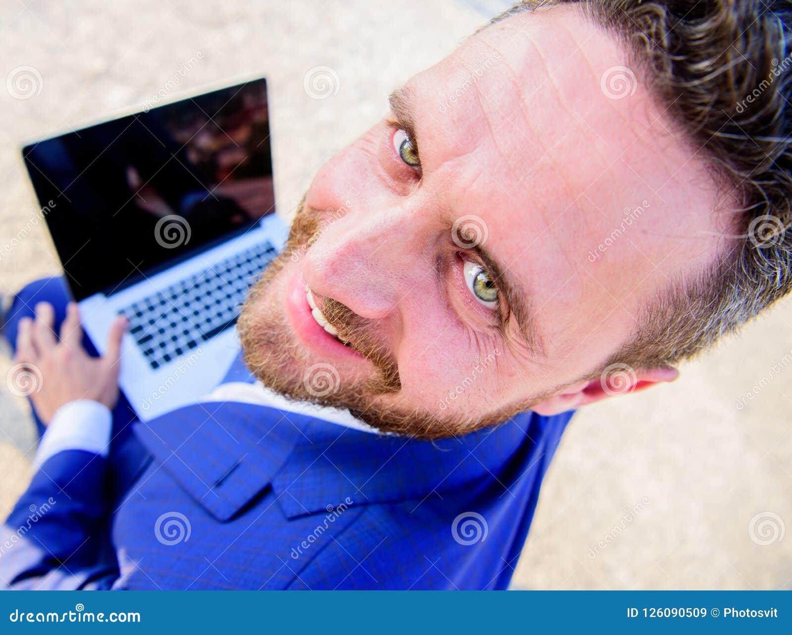 宜人的工作日户外 商人正式衣服神色,当举行打开屏幕膝上型计算机时 人微笑的快乐的面孔