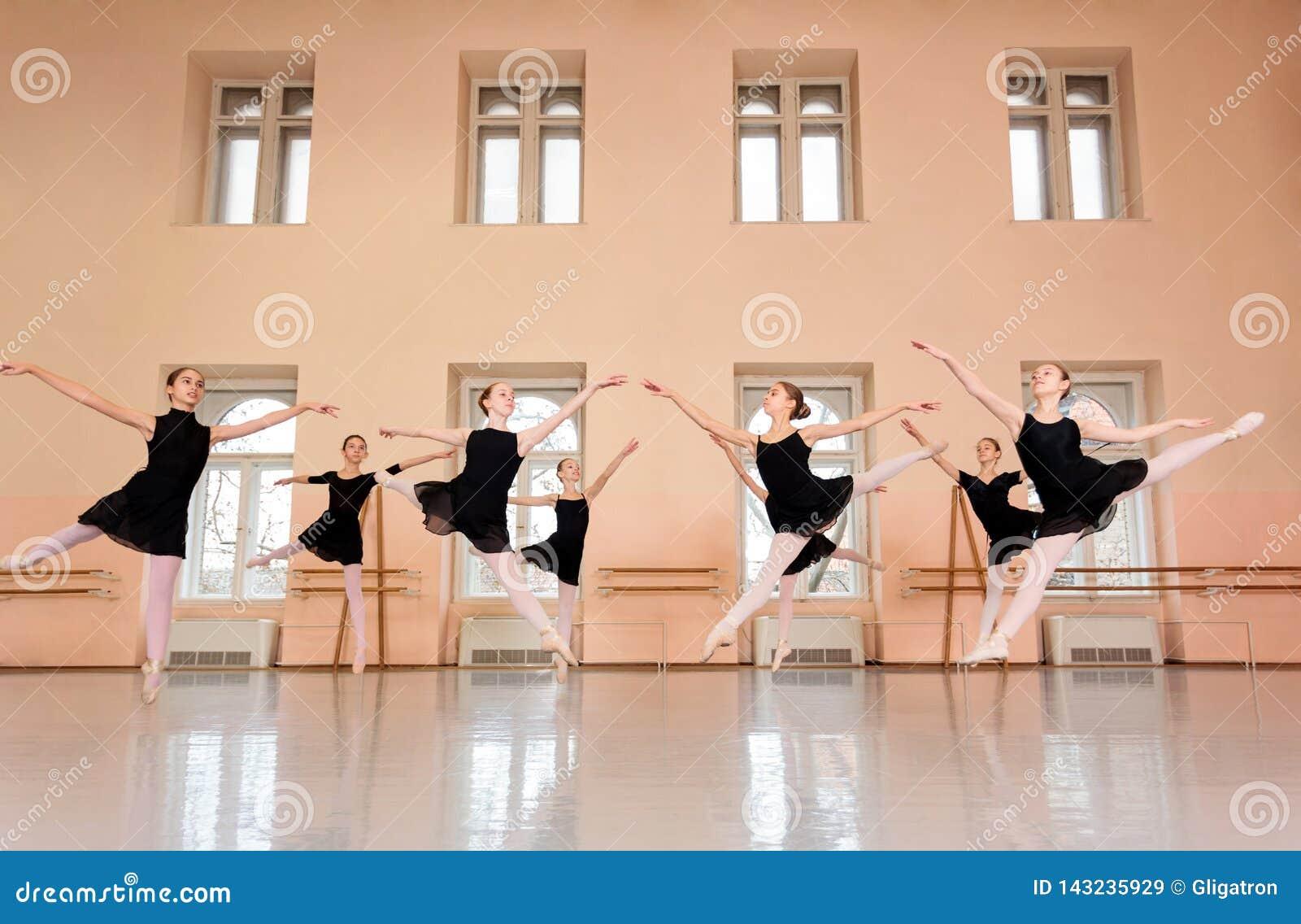 实践古典芭蕾的中等小组十几岁的女孩在一个大跳舞的演播室