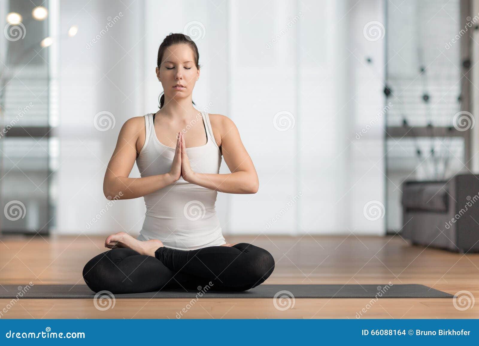 少妇实践的瑜伽在家在地板上和做莲花摆在.图片