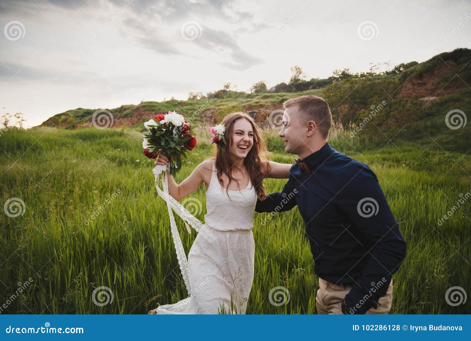 室外婚礼、时髦的愉快的微笑的新郎和新娘是笑和看彼此在绿色领域