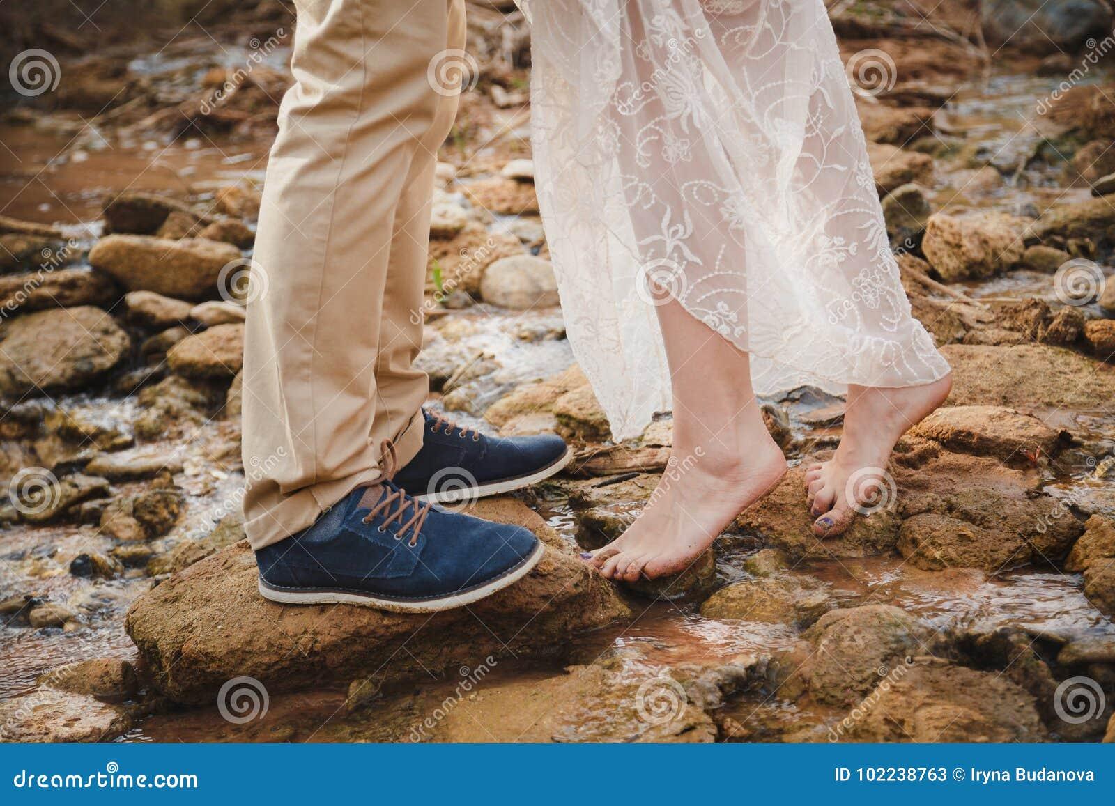 室外婚礼,关闭赤足站立在石头的少妇脚在前面人穿深蓝鞋子的脚