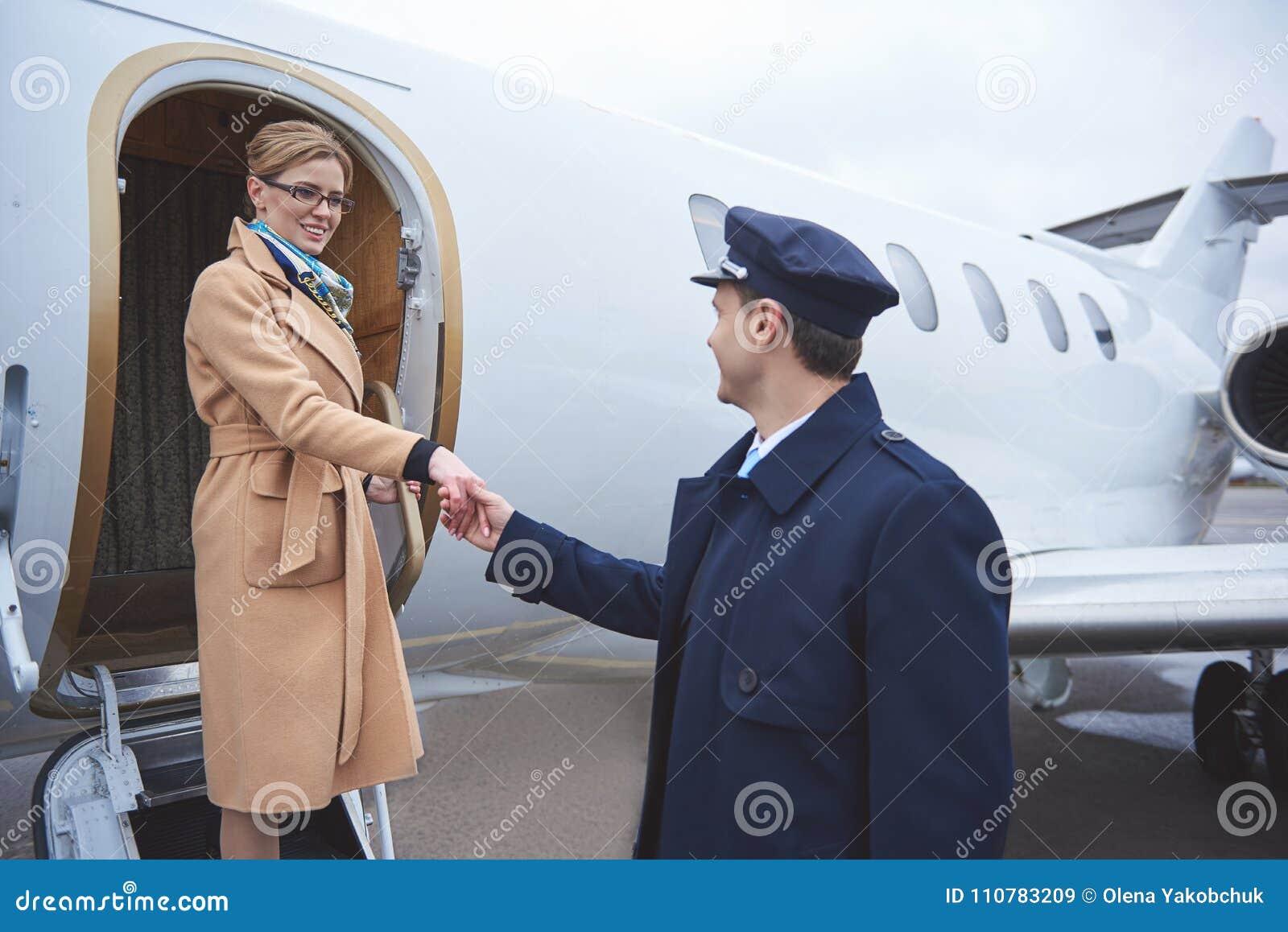 室外快乐的夫人问候的飞行员