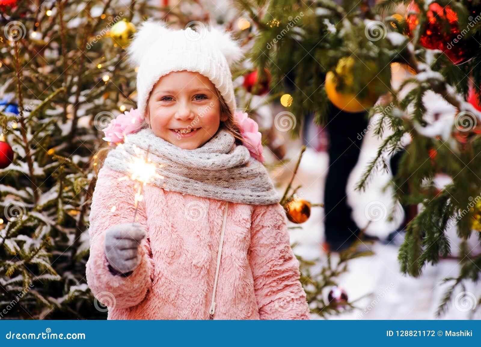 室外愉快的儿童女孩拿着灼烧的闪烁发光物的或的烟花圣诞节画象