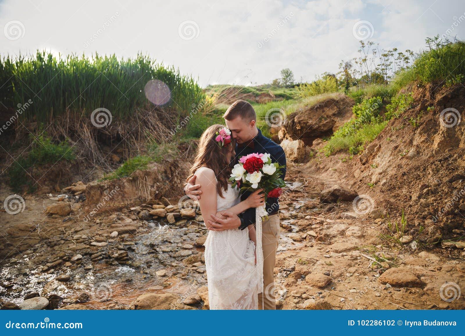 室外海滩婚礼仪式、时髦的愉快的微笑的新郎和新娘是站立和拥抱在小河附近
