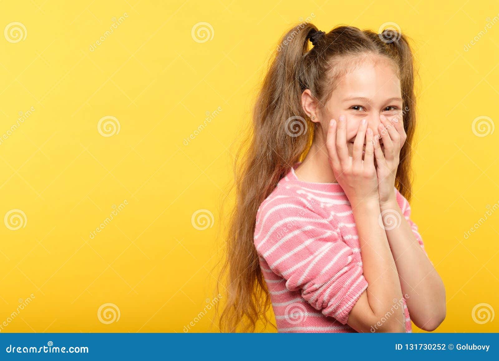 害羞的微笑的窘迫女孩覆盖物嘴手