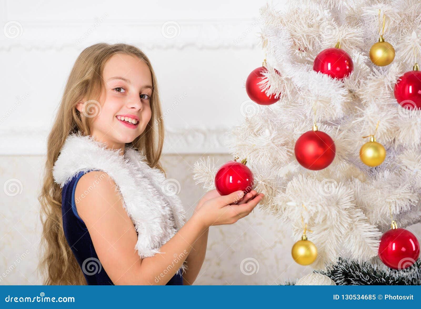 家庭假日概念 女孩天鹅绒礼服感到欢乐在圣诞树附近 传播圣诞节欢呼 愉快的孩子,因为