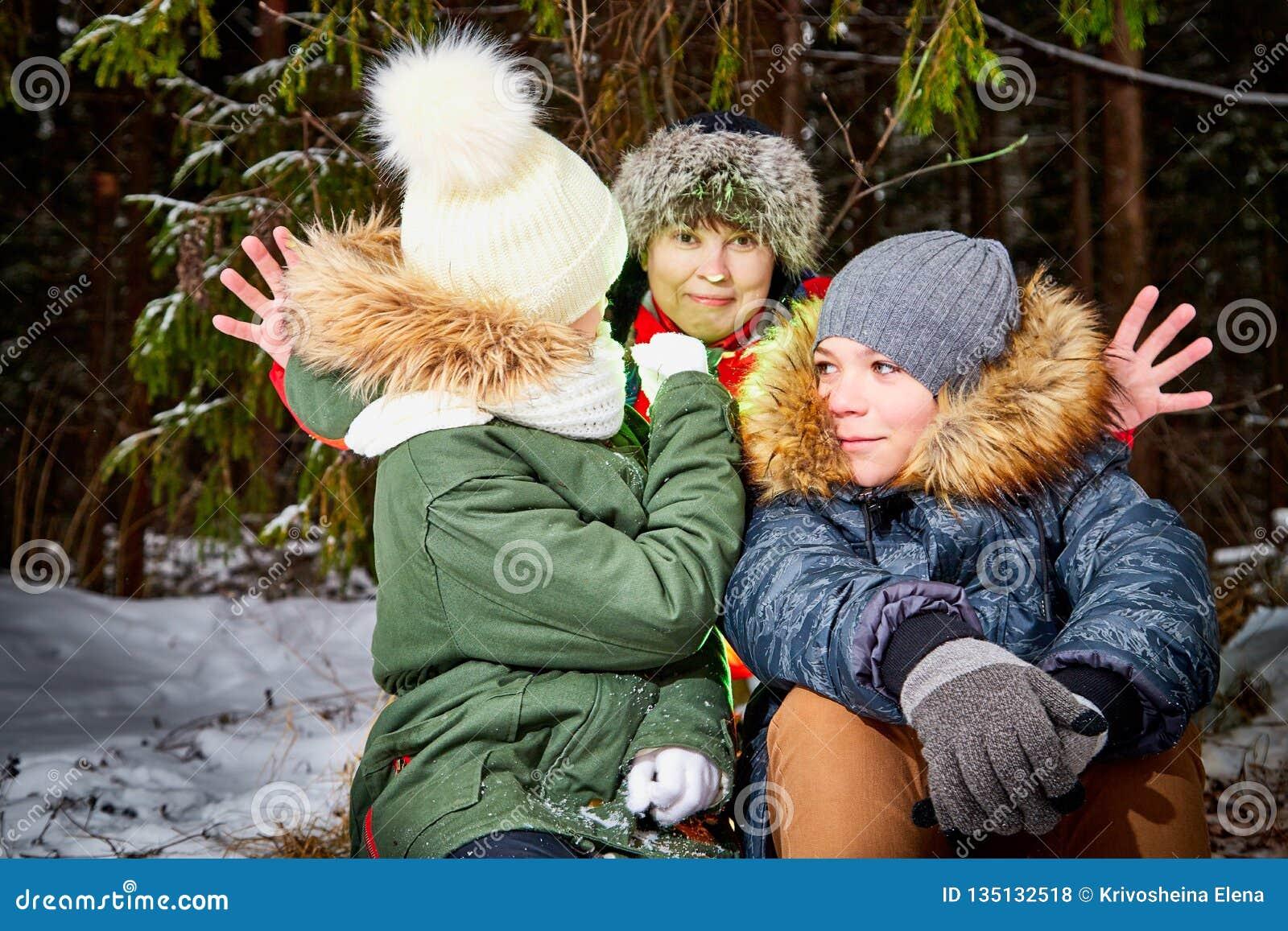 家庭包括妈妈、男孩和女孩在雪森林里在一个冬日 有的少年和的母亲室外的野餐