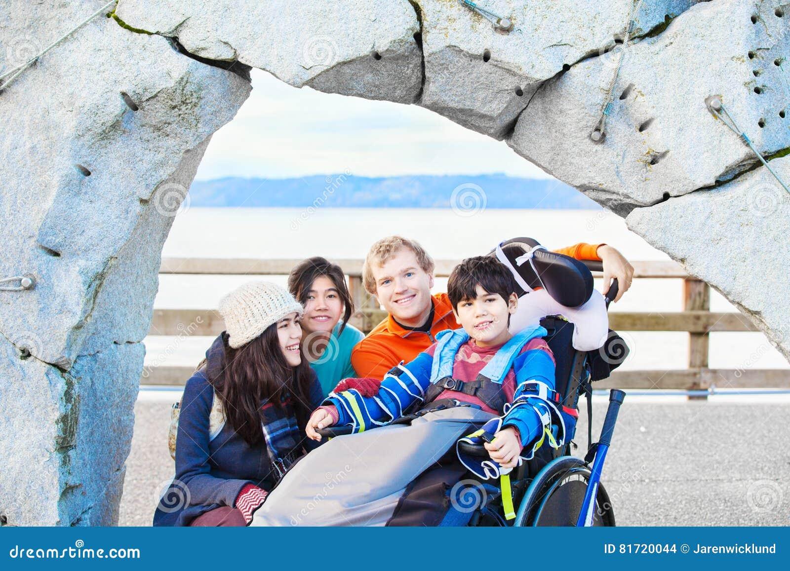 家庭和朋友outd围拢的轮椅的残疾男孩