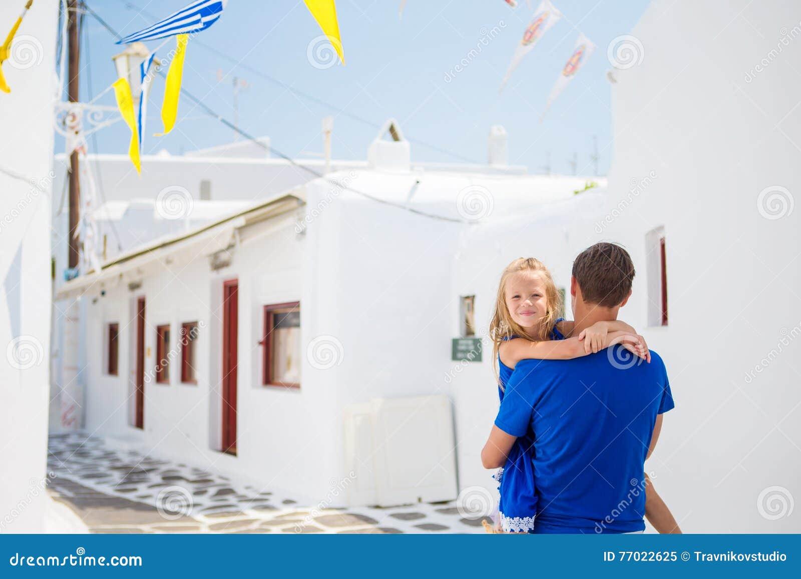 家庭在欧洲 愉快的父亲和小可爱的女孩在夏天希腊语期间的米科诺斯岛假期