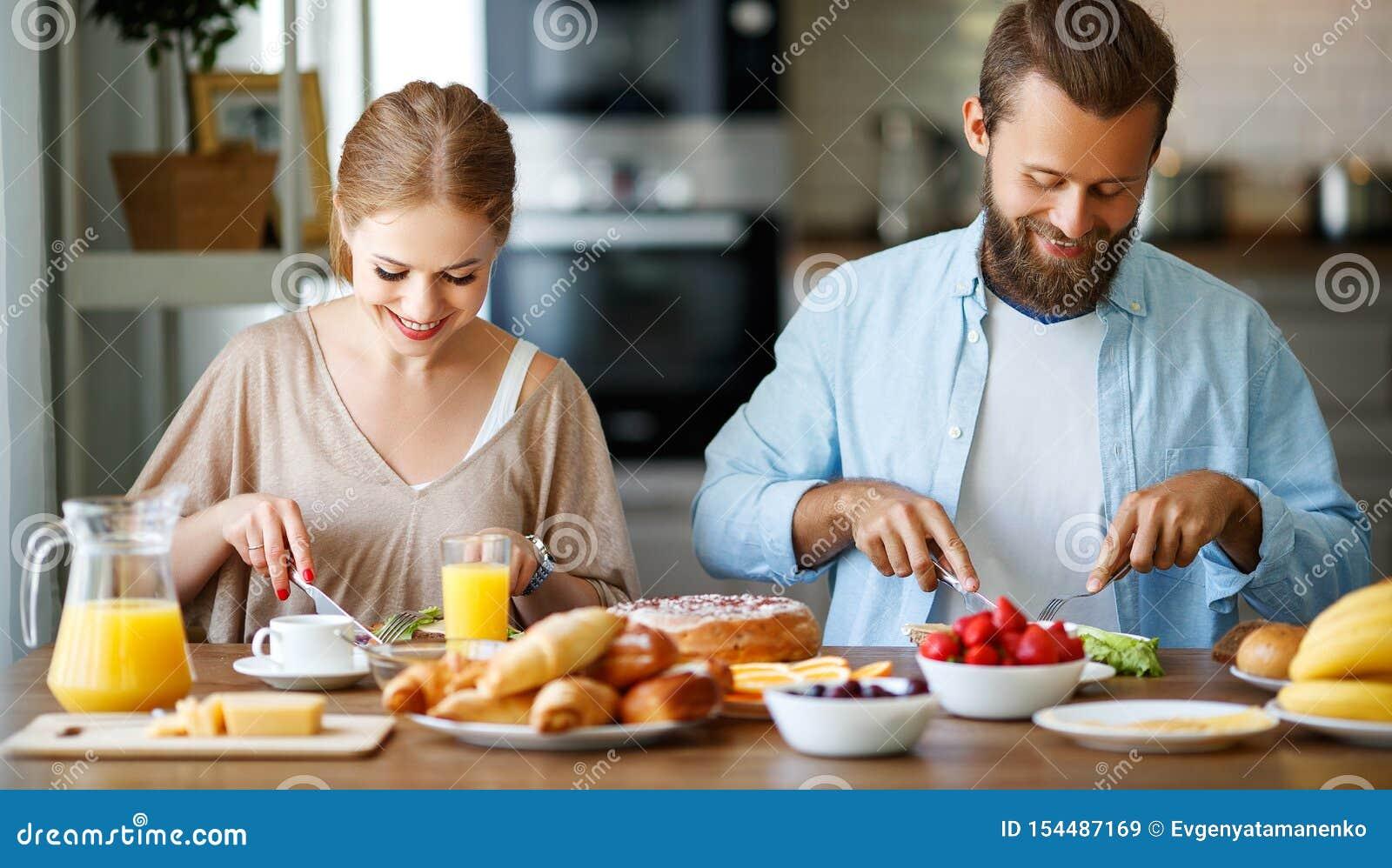 家庭愉快的夫妇食用早餐在厨房在早晨