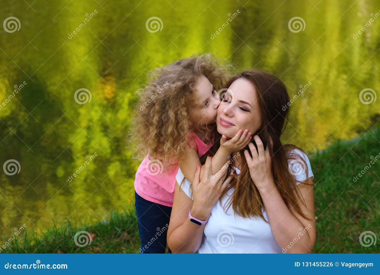 家庭时间 母亲和女儿河岸的 女孩拥抱并且亲吻母亲