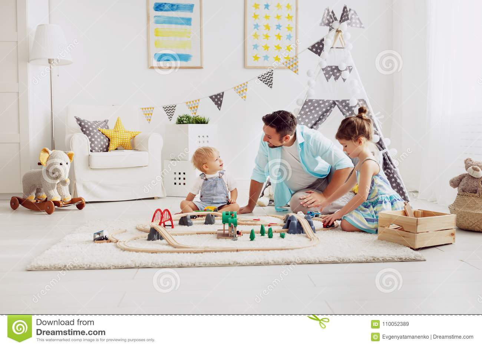 家庭父亲和孩子播放在游戏室的一条玩具铁路