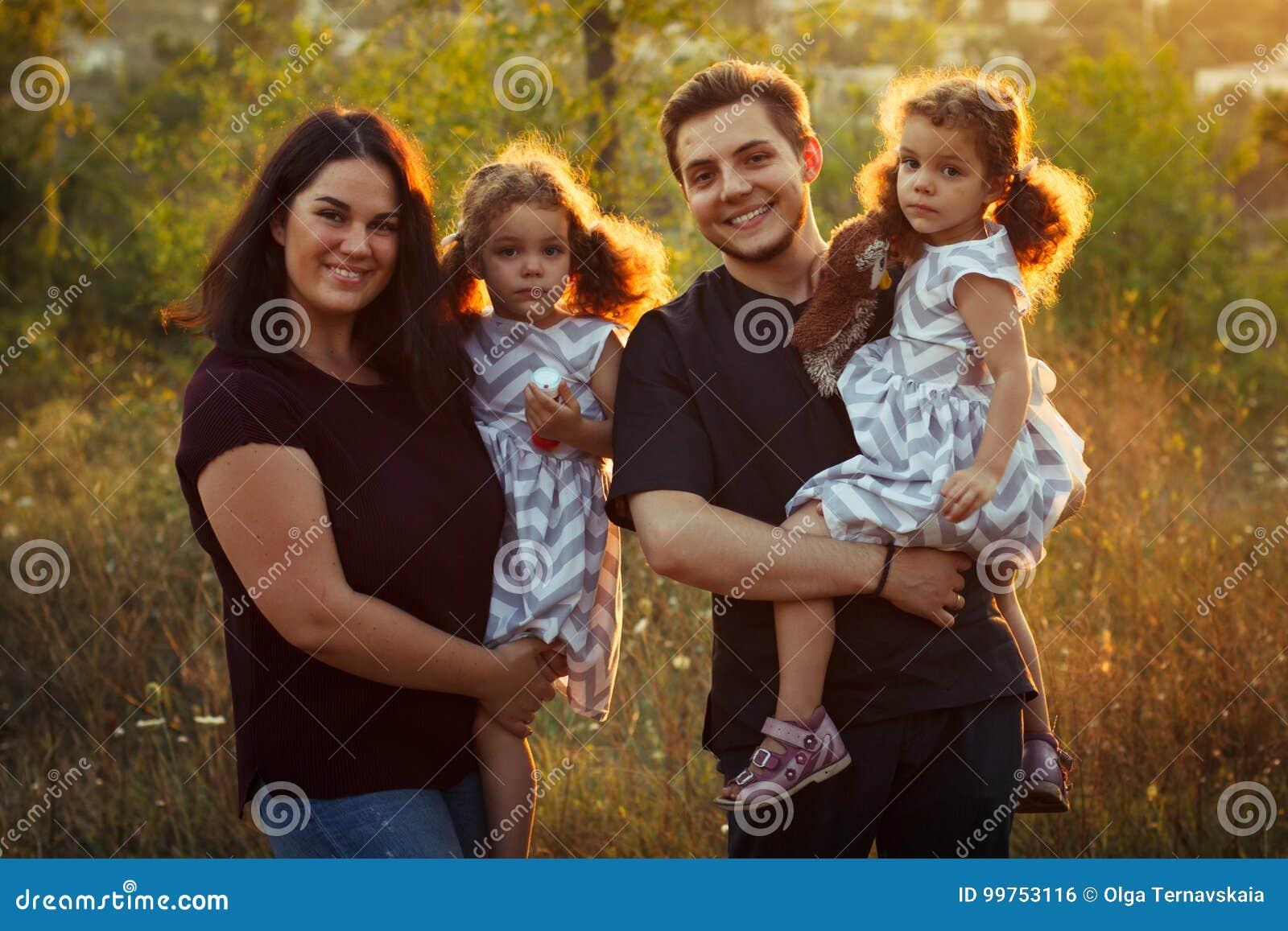 家庭画象四在与小女孩的秋天森林公园孪生 愉快的人民,微笑和亲吻 温暖的晚上阳光