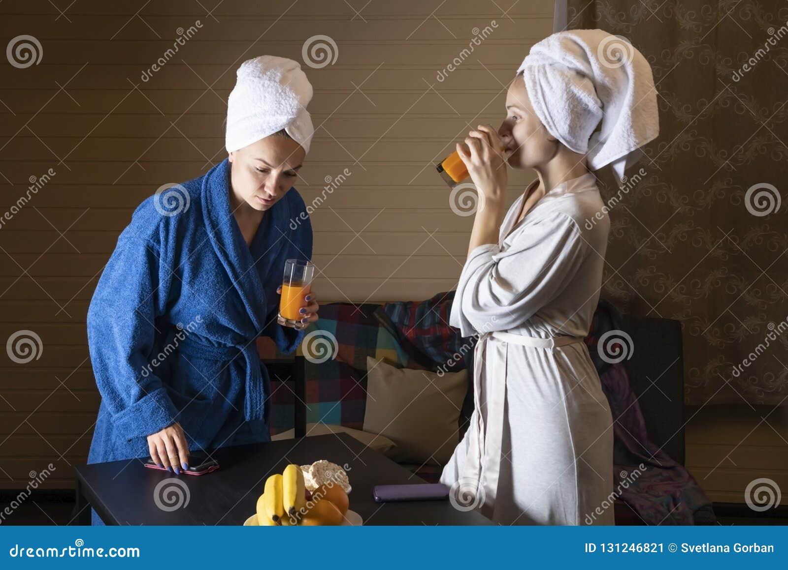 家庭衣裳的妇女喝汁液