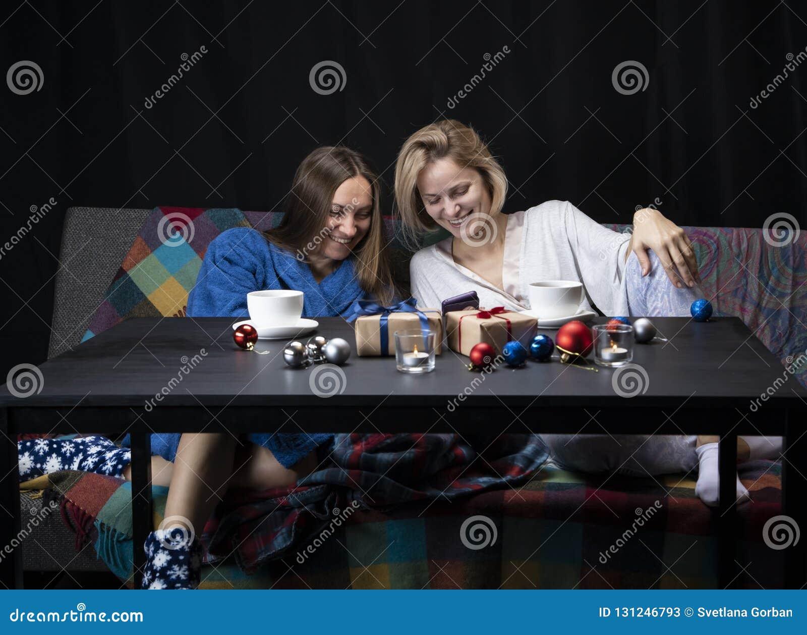家庭衣裳的妇女喝茶 黑色背景