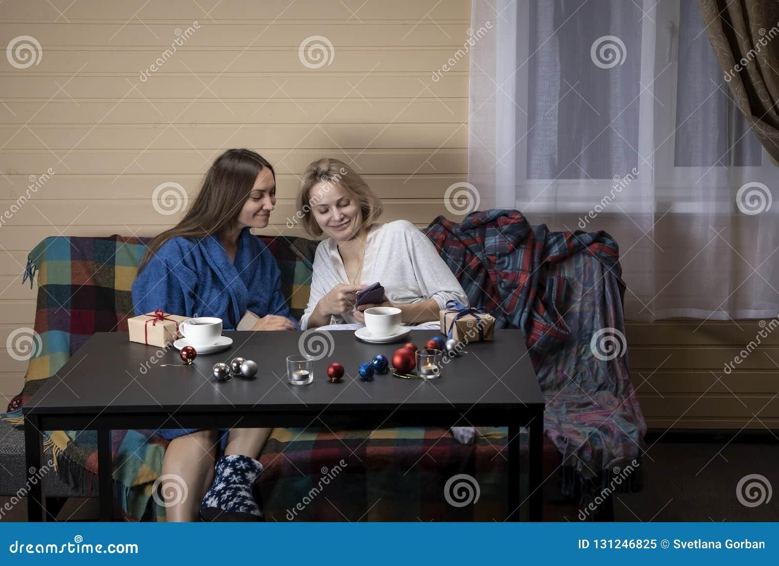 家庭衣裳的妇女喝茶