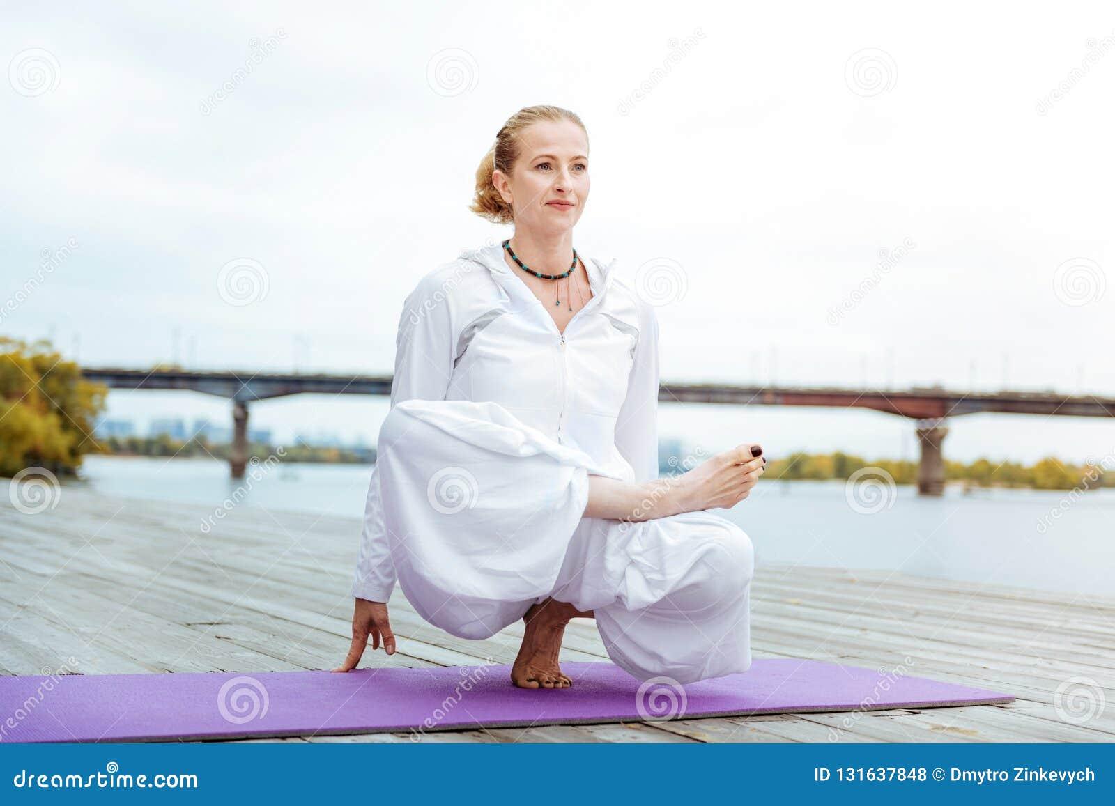 容易地实践复杂的asanas的女性瑜伽辅导员