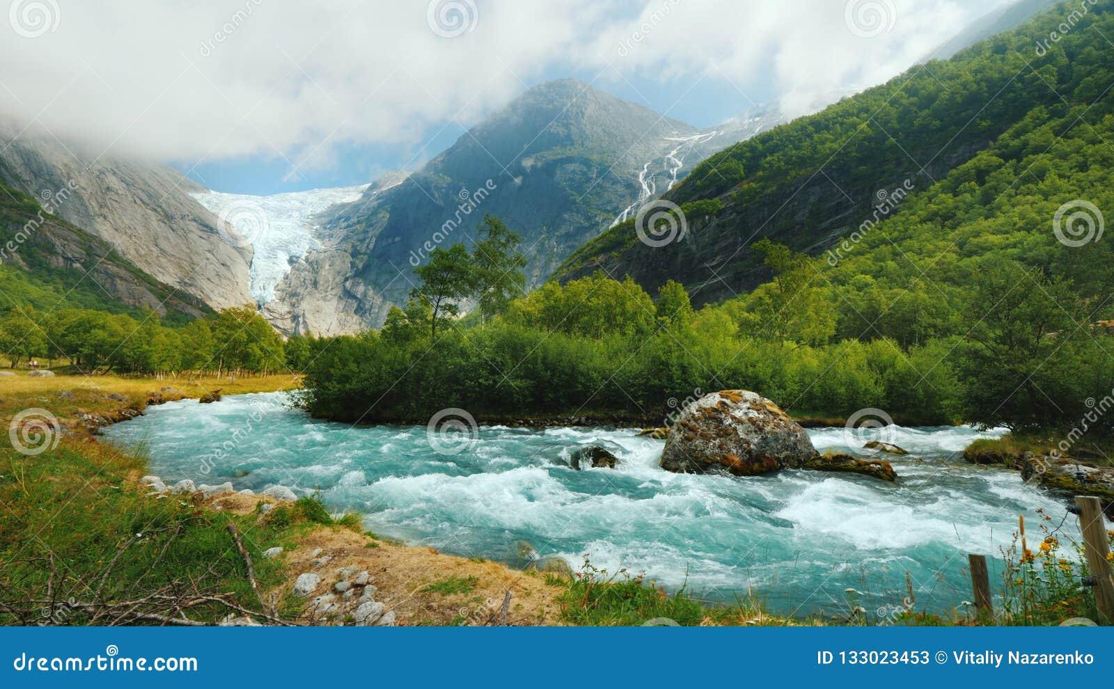 宽透镜射击:与一条山河的Briksdal冰川前景的 挪威的惊人的本质